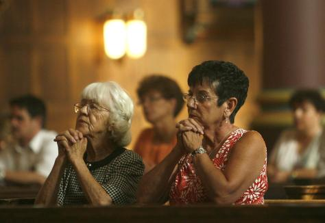 Philippine Cannefax, left, and Joyce Lowe pray during a special Mass at the Catholic Diocese of Salt Lake City Wednesday, Aug, 8, 2007, in Salt Lake City. The Mass was held for the six trapped coal miners at the Crandall Canyon mine. (AP Photo/Salt Lake Tribune, Al Hartmann) ** THE DESERET MORNING NEWS OUT, NO MAGS, NO SALES **